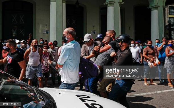 Man is arrested during a demonstration against the government of Cuban President Miguel Diaz-Canel in Havana, on July 11, 2021. - Thousands of Cubans...