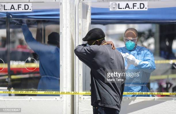 A man is asked to cough into his arm as part of testing for COVID19 by a member of the Los Angeles Fire Department wearing personal protective...