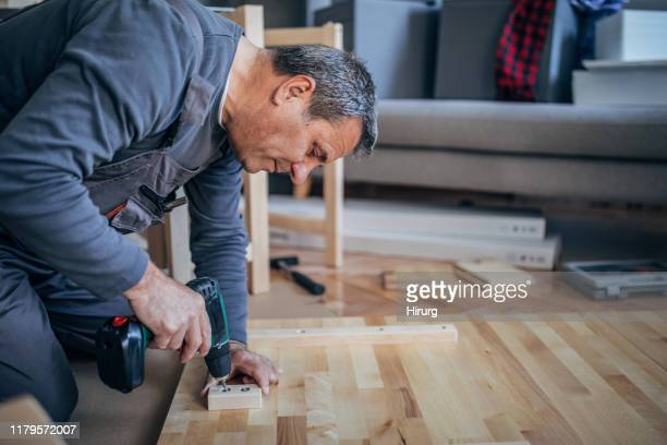 man is assembling furniture with drill - dungarees stock pictures, royalty-free photos & images