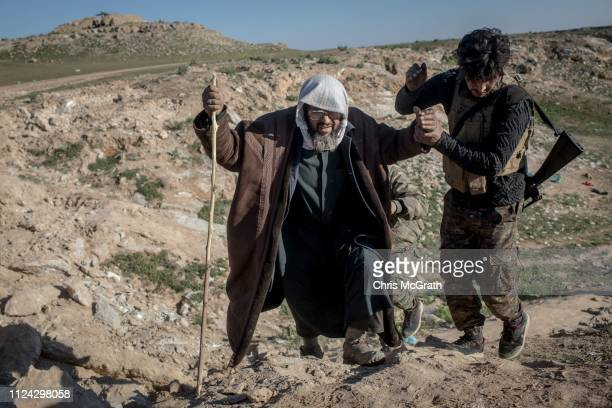 Man is assisted by an SDF fighter after arriving at an SDF position on the outskirts of Bagouz after walking hours to flee fighting on February 12,...