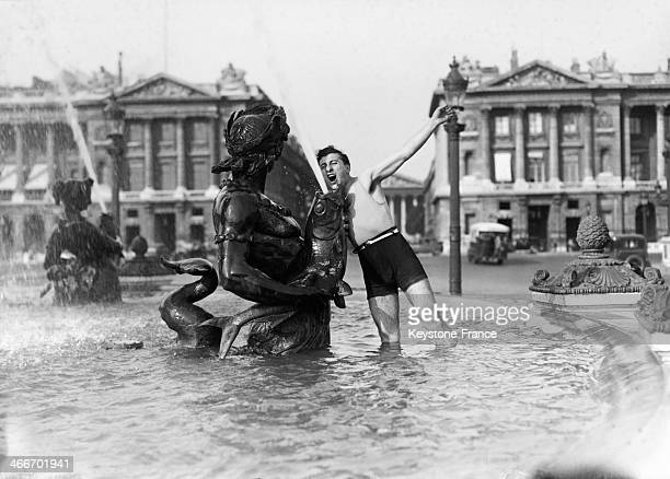 A man is bathing in a fountain on the Place de la Concorde during the heatwave in September 1929 in Paris France