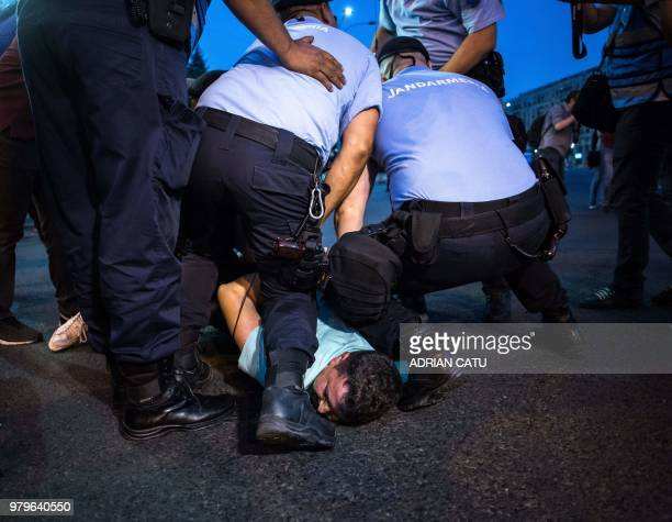 A man is being arrested by riot police in front of the prime minister's office in Bucharest Romania on June 20 2018 during a protest against...