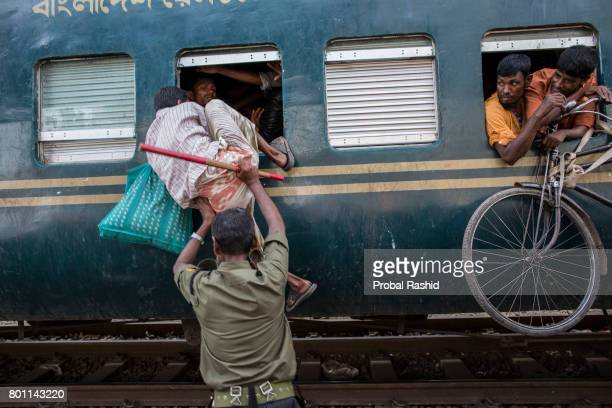 DHAKA BANGLADESH DHAKA BANGLADESH A man is being pushed towards a train compartment's window while other people on the roof of the train as they...