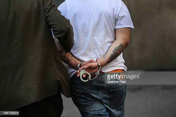 A man is brought to jail by a New York City Police Officer on July 10 2012 in New York City Both New York and Chicago have recently witnessed spikes...