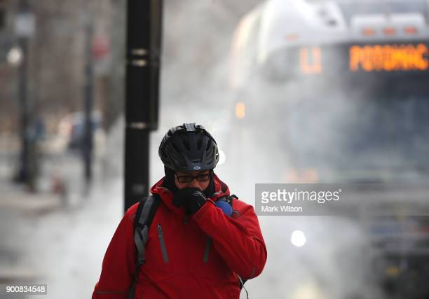 A man is bundled up as he walks past a steam grate on January 3 2018 in Washington DC A winter storm is traveling up the east coast overnight with...