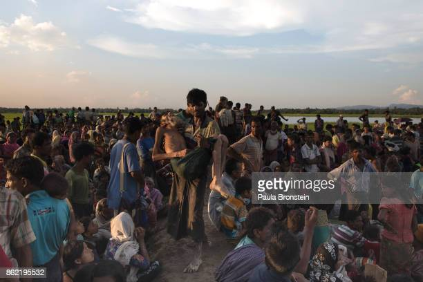 A man is carried after collapsing from dehydration as thousands of Rohingya refugees flee from Myanmar are kept under a tight security by Bangladeshi...