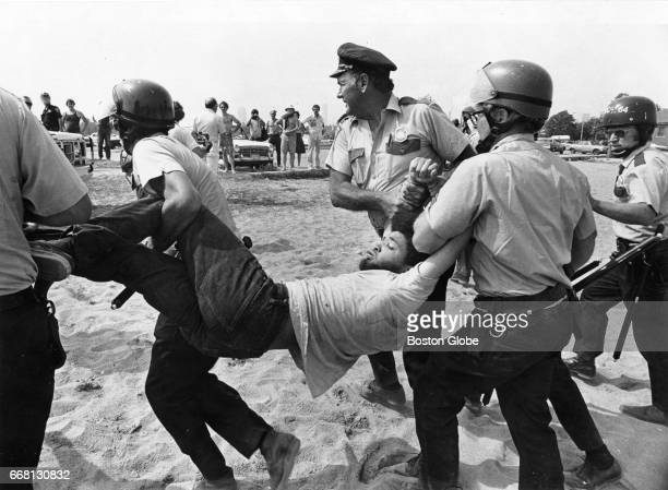 A man is carried by Boston Police officers on Carson Beach in South Boston on Aug 10 1975 Hundreds of officers were on hand to quell a disturbance...