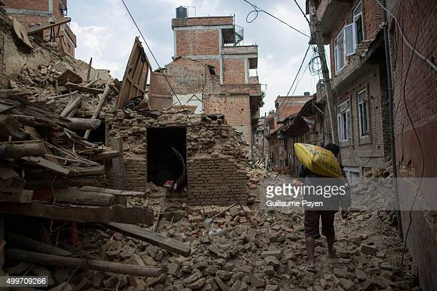 KHOKANA KATHMANDU CENTRAL NEPAL A man is carrying a big rice bag as he pass through the rubbles from collapsed houses in the Khokana Village south of...