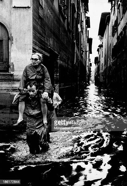 A man is carrying an old woman on his shoulders through a flooded street between the palaces of Florence the city has been seriously affected by an...