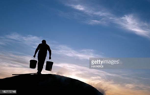 man is carrying water at rural area - bucket stock pictures, royalty-free photos & images