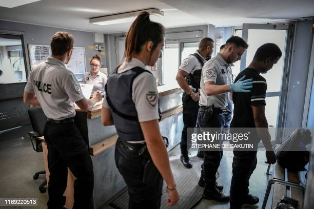 Man is checked by police officers prior to his integration at the 'Centre de Retention Administrative' , a migrant detention centre in Vincennes,...