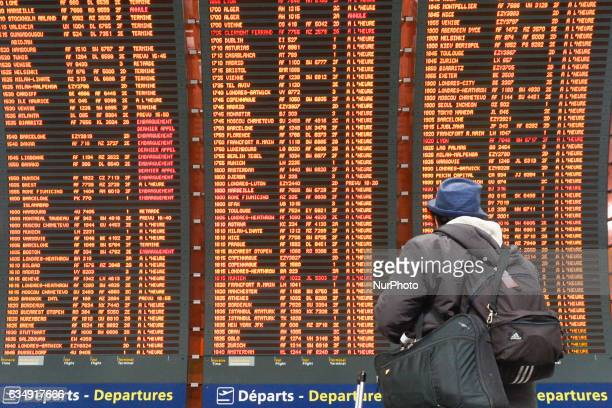 Man is checking his flight on the Departures board at the Terminal 2 of Paris Charles de Gaulle Airport. On Sunday, 12 February in Paris, France.