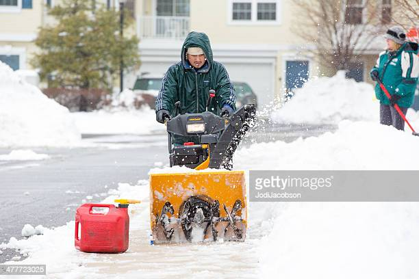 Man is clearing snow with a snowblower