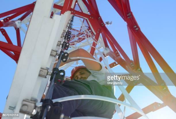 man is een krachtige elektrische lijn toren beklimmen - tuig mast stockfoto's en -beelden