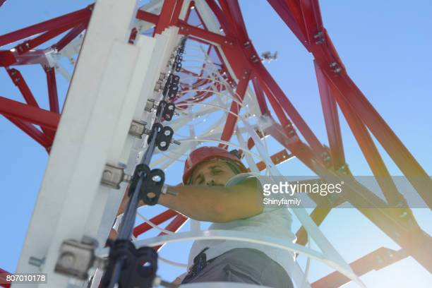 Man is climbing a high power electric line tower