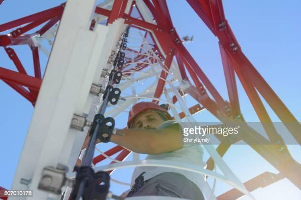 homem é escalar uma torre de linha elétrica de alta potência - poste - fotografias e filmes do acervo