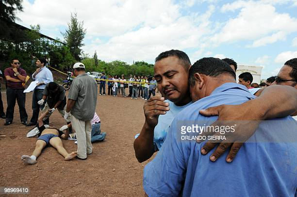 Man is comforted as he cries at the sigh of his son, Universidad Nacional Autonoma de Honduras student Moises Antonio Andrade Hernandez , found...