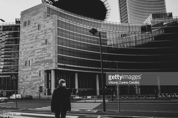 A man is crossing the street in front of the Lombardy Region building March 10 2020 in Milan Italy The Italian Government has strengthened up its...