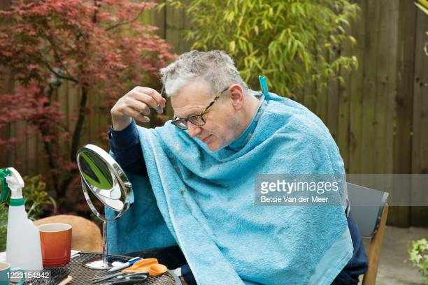 man is cutting his hair during lockdown in back garden. - cutting stock pictures, royalty-free photos & images