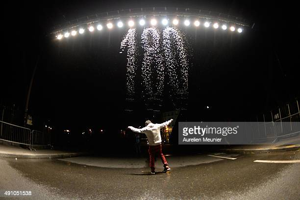 A man is dancing under thousands of water drops creating a cascade of words a creation by german artist Julius Popp named 'BitFall' during the 'Nuit...
