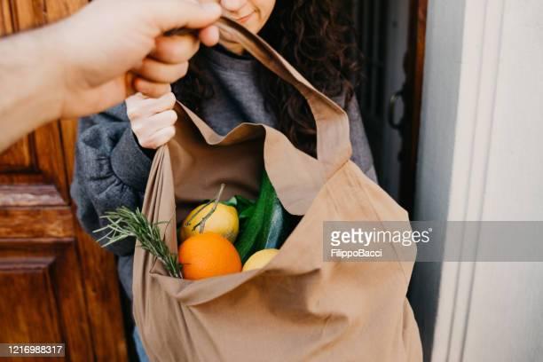 un hombre está entregando una bolsa de verduras y frutas - dar fotografías e imágenes de stock