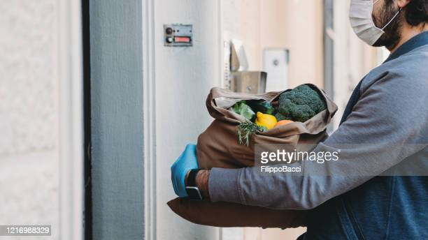 a man is delivering a bag of vegetables and fruit - helping hand stock pictures, royalty-free photos & images