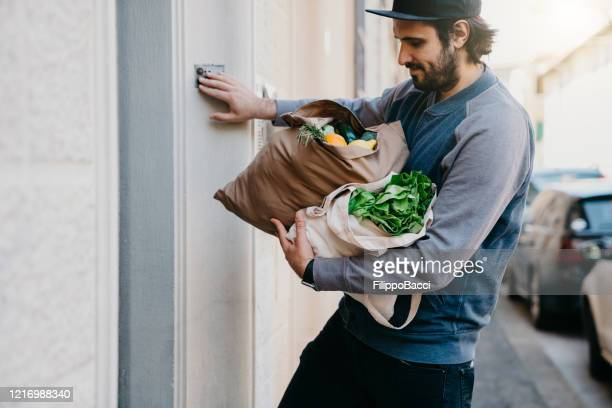 a man is delivering a bag of vegetables and fruit - ringing doorbell stock pictures, royalty-free photos & images