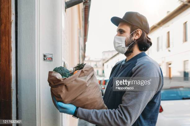 a man is delivering a bag of vegetables and fruit - illness prevention stock pictures, royalty-free photos & images
