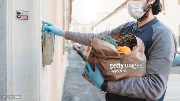 a man is delivering a bag of vegetables and fruit - aplanar a curva imagens e fotografias de stock