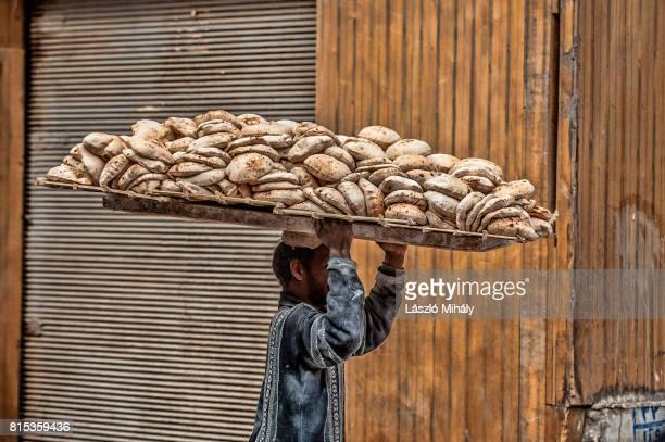 man is delivering bread in cairo egypt - zamalek photos et images de collection