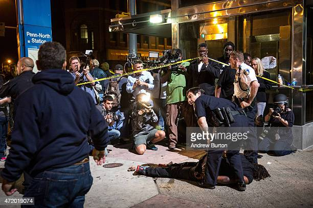 A man is detained after being pepper sprayed in the face by police at the end of a day of protests in the Sandtown neighborhood where Freddie Gray...