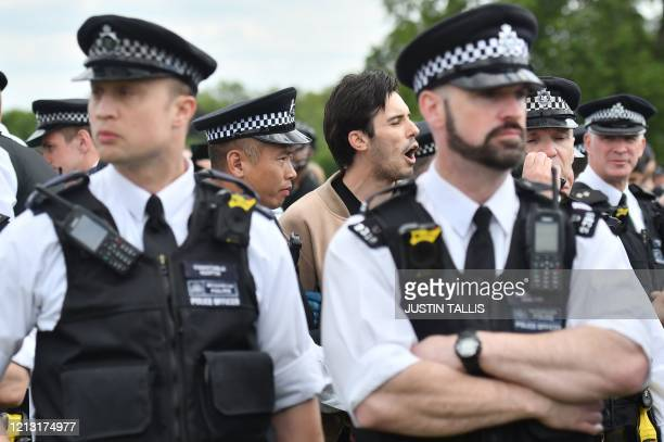 Man is detained and led away in handcuffs by police officers at an anti-coronavirus lockdown demonstration in Hyde Park in London on May 16 following...