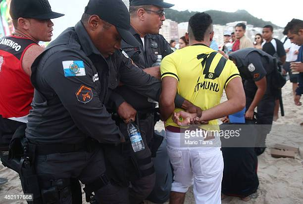 A man is detained by military police following reports of pickpocketing on Copacabana Beach during the 2014 FIFA World Cup final match pitting...