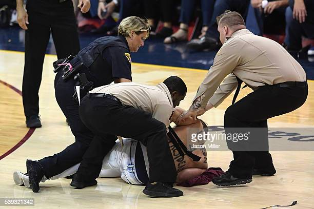 A man is detained by police and security after running onto the court during the second half in Game 4 of the 2016 NBA Finals between the Cleveland...
