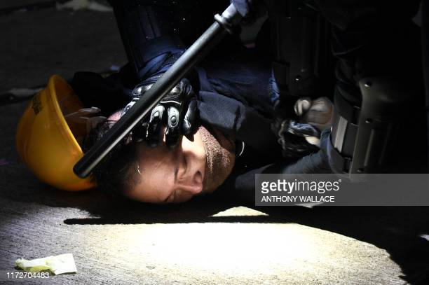TOPSHOT A man is detained by police during clashes in the Wanchai district in Hong Kong on October 1 as the city observes the National Day holiday to...