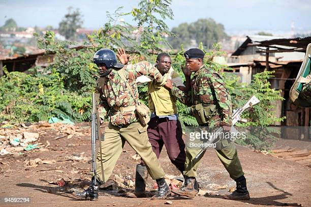 A man is detained by police officers in the Kibera area of Nairobi Kenya on Friday Jan 18 2008 Kenyan police shot dead four people in Kibera during...
