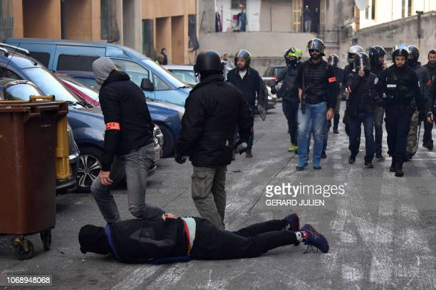 A man is detained by police officers on December 6 2018 in Marseille southern France on the sideline of a demonstration of high school students...