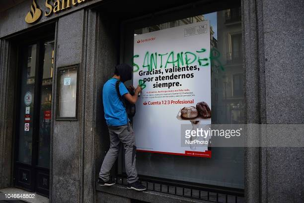 A man is doing a painting In a bank branch during a demonstration for the right to adequate housing and against evictions and mortgage abuse in...