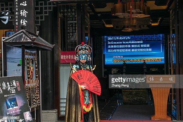 Man is dressed up as a face-changing performer outside a teahouse to attract tourists. Face-Changing opera is an ancient Chinese dramatic art that is...
