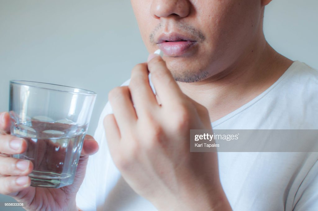 A man is drinking a medicine pill : Stock Photo