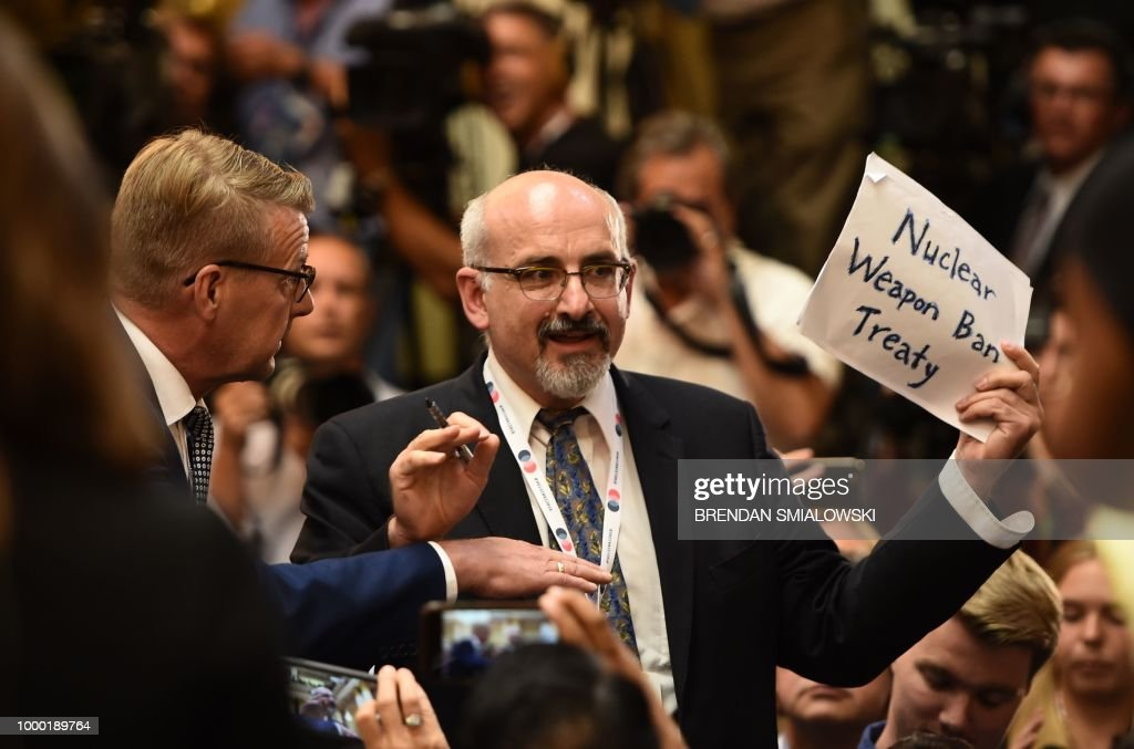 TOPSHOT - A man is escorted out of the press conference room for having a sign reading 'Nuclear weapon Ban Treaty' ahead a joint press conference of the US and Russian presidents after a meeting at the Presidential Palace in Helsinki, on July 16, 2018. - The US and Russian leaders opened an historic summit in Helsinki, with Donald Trump promising an 'extraordinary relationship' and Vladimir Putin saying it was high time to thrash out disputes around the world.