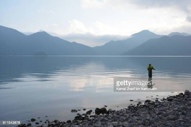 A man is fishing beside the lake