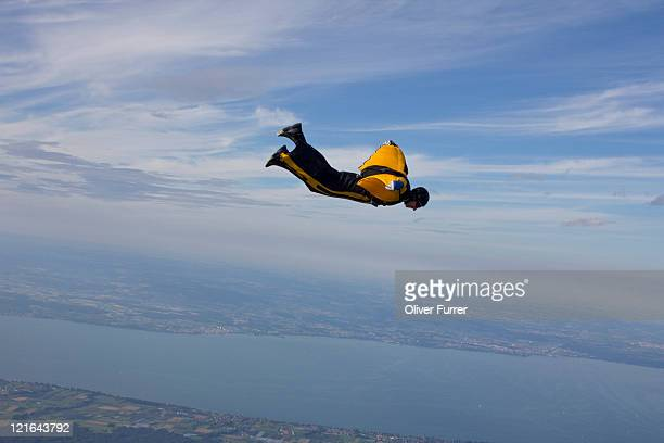 Man is flying in yellow jumpsuit with wings.