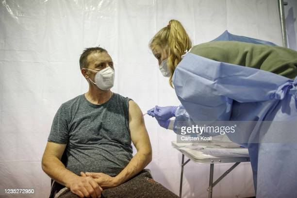 Man is given a dose of the Moderna vaccine in a temporary vaccination center, where a voucher for a doner kebab is issued after the vaccination, on...