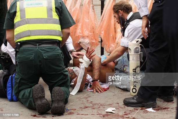 A man is given emergency medical treatment by police officers and paramedics after being stabbed in the stomach at the Notting Hill Carnival on...
