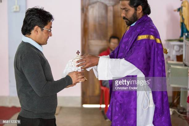 A man is giving a jar to a priest while a ceremony inside a church in Kalimpong