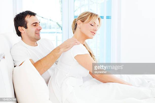 man is giving a massage to his wife in bedroom. - husband massage wife stock photos and pictures