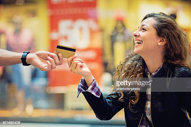 Man is giving credit card to his girlfriend