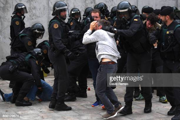 A man is grabbed by officers as police move in on the crowds as members of the public gather outside to prevent them from stopping the opening and...