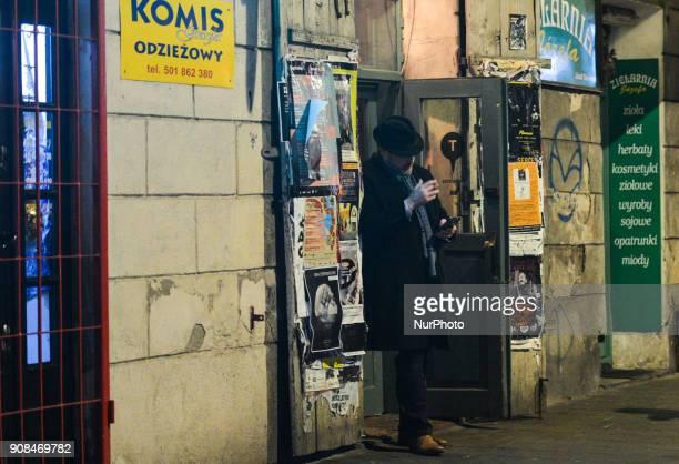 A man is having a smoke outside a pub in Kazimierz area of Krakow On Sunday 21 January 2018 in Krakow Poland